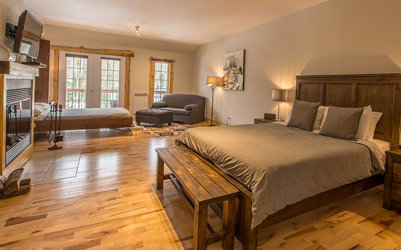 Luxurious room with a king size bed and wood fireplace  - Auberge du Vieux Moulin